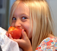 Young girl enjoying a fresh peach.